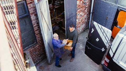Two men in front of a workshop door, viewed from a bird's eye perspective