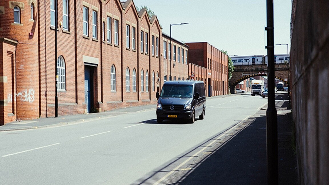 A black Sprinter driving along a road lined with brick-built buildings