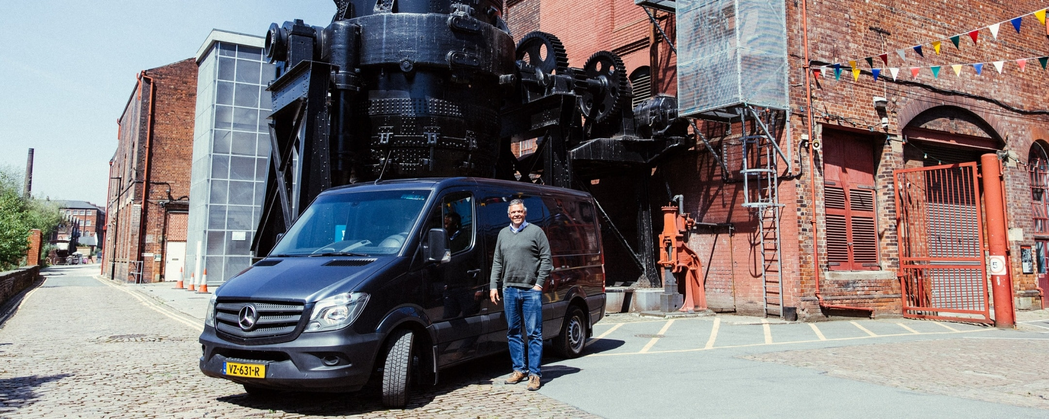 A man standing next to a black Sprinter in an industrial estate